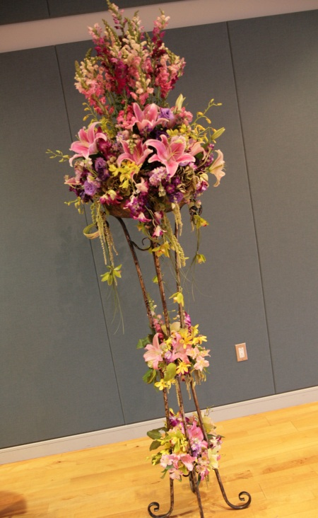 Rusty wrought iron stands were adorned with tiers of draping florals.