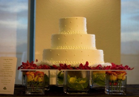 A clean white cake placed on a bed of roses and orchids.  How sweet!