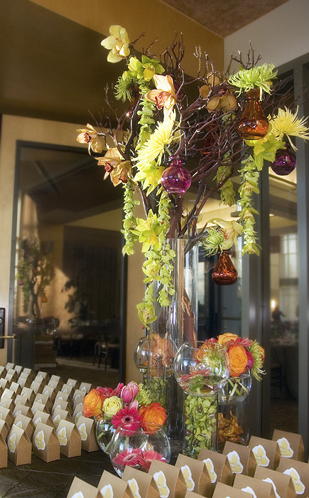 A wild and playful escort card table arrangement, with dangling orchids and a collection of vases.