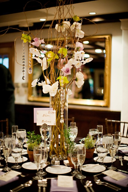 This centerpiece featured cymbidiums, phaleonopsis, and roses wired onto curly willow.