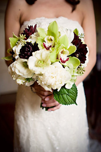 Yummy white lisianthus, roses, and anenomes, with pops of lime orchids and black dahlias.